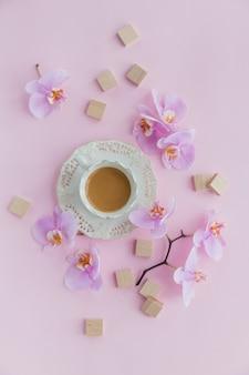 Чашка чая и летающие цветы орхидеи на светло-розовом