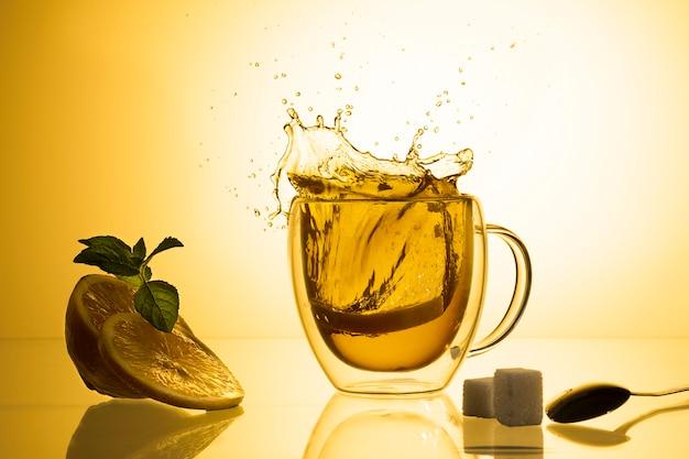 Чашка чая и стеклянный чайник на стекле с оранжевым фоном.