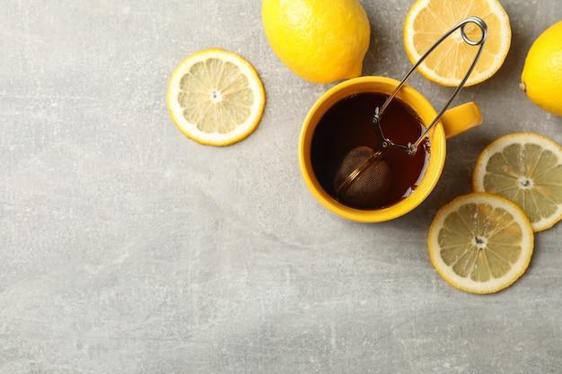 Чашка чая и лимоны на сером, место для текста