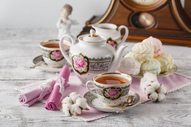 一杯のお茶と白いテーブルの上のティーポットとマシュマロ