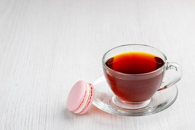 밝은 나무 배경에 차와 핑크 마카롱 컵