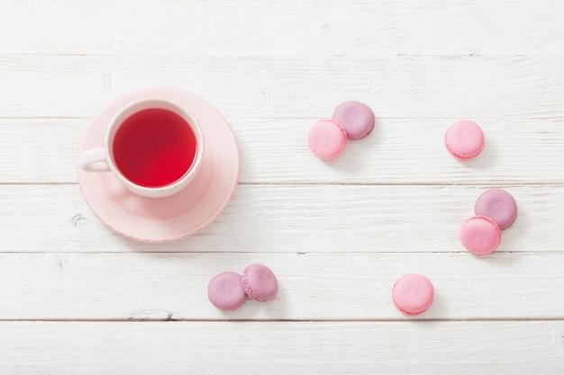 Чашка чая и розовые миндальное печенье на белом деревянном столе