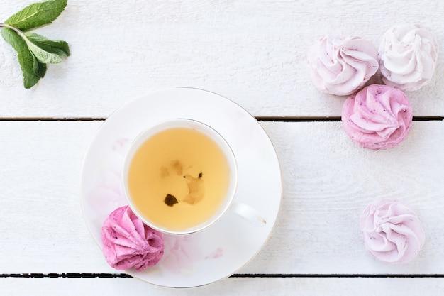 一杯のお茶とピンクのマシュマロと緑茶白。食物。菓子および飲料