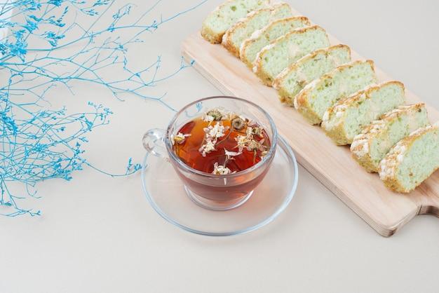 白い表面にお茶とピスタチオのケーキのスライスのカップ