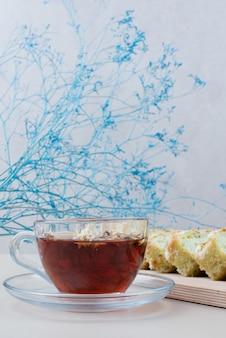 白のお茶とピスタチオのケーキのスライスのカップ。