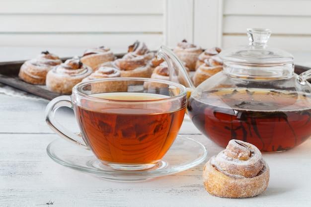 一杯のお茶と小さなリンゴのバラの形をしたパイ。甘いリンゴのデザートパイ。自家製アップルローズペストリー。甘いリンゴのペストリーと朝食のお茶