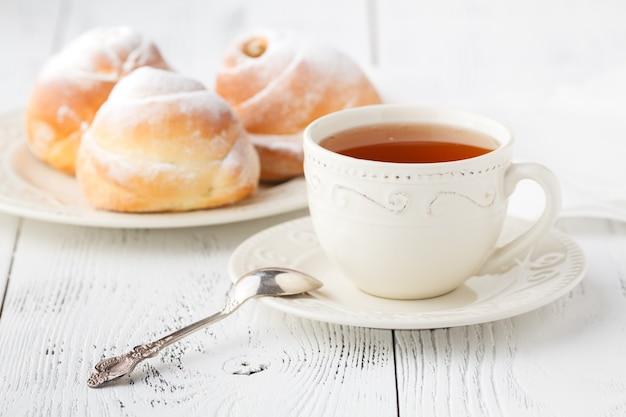 一杯のお茶と小さなリンゴのバラの形をしたパイ。甘いりんごのデザートパイ
