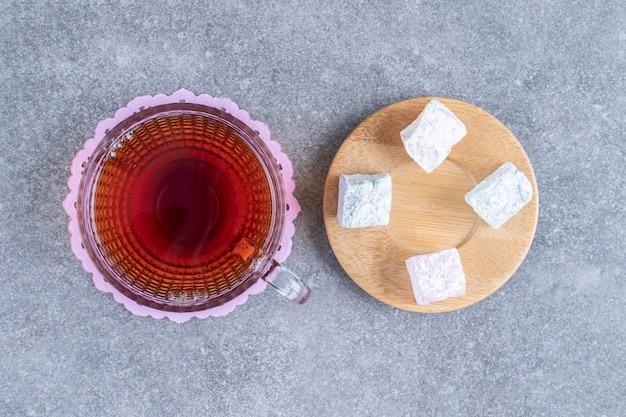Чашка чая и мягкие конфеты на мраморной поверхности