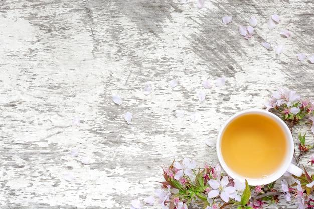 一杯のお茶と花びらを持つ白い素朴な木製のテーブルに春の桜や桜の花
