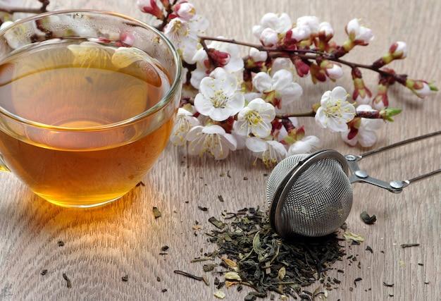 木製のテーブルにお茶と春の花のカップ