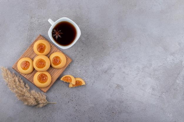 돌 테이블에 차와 달콤한 라운드 쿠키 컵.