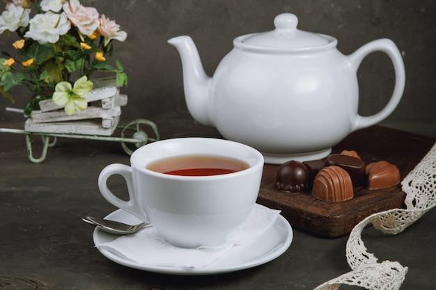 Чашка чая и чайник и шоколадные конфеты на черном фоне