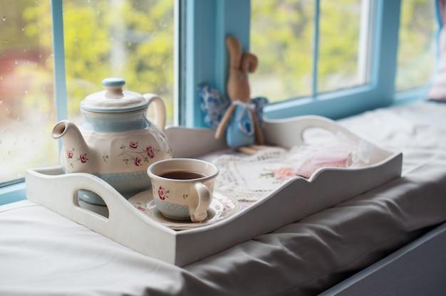 一杯の紅茶と木製トレイ上のティーポットをクローズアップ