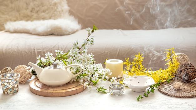 居心地の良い明るい部屋のぼやけたテーブルに春の花とお茶とティーポットのカップ。