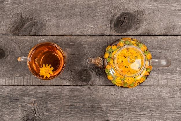 나무 배경에 금송화 꽃이 있는 차 한 잔과 투명한 찻주전자. 금송화 차는 건강 개념에 도움이 됩니다. 평면도.