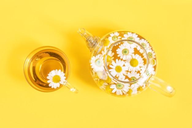 Чашка чая и прозрачный чайник с цветами ромашки на желтом фоне. ромашковый чай приносит пользу вашему здоровью. вид сверху.