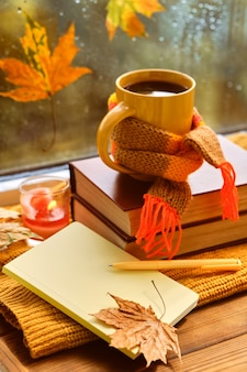 Чашка чая, осенние листья, книги, тетрадь и красный вязаный плед на деревянном столе