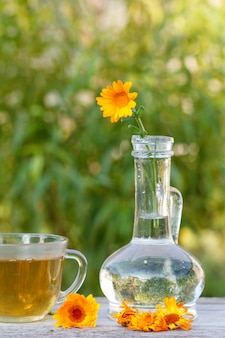 차 한 잔, 유리 플라스크에 줄기가 있는 금송화 꽃, 흐릿한 녹색 자연 배경이 있는 나무 판자에 같은 꽃
