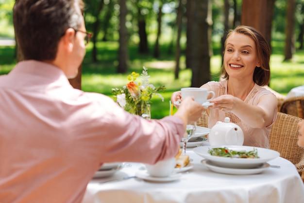 Чашка чая. заботливая любящая жена чувствует себя прекрасно, подавая чашку чая своему мужу в воскресенье утром
