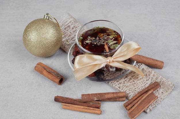 白いテーブルの上にお茶、シナモンスティック、お祝いのボールのカップ。高品質の写真