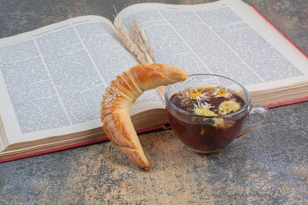 大理石の表面にお茶、クッキー、本を一杯