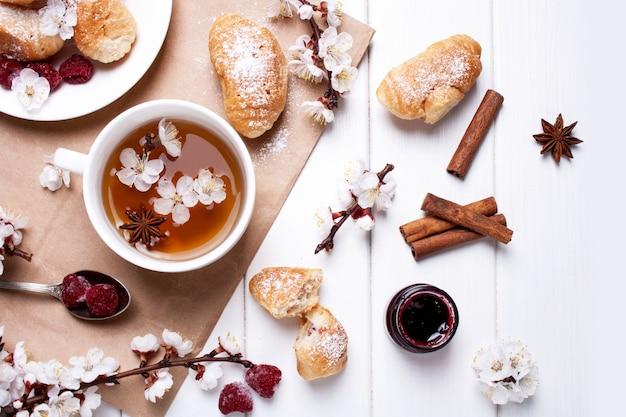 白い木製の背景にお茶、クロワッサン、春の花の枝のカップ。フラットレイスタイル