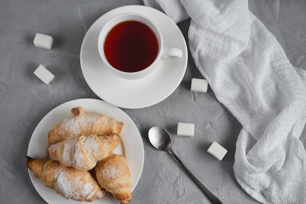 Чашка чая, круассаны, кубики сахара на сером фоне, концепция завтрака, вид сверху