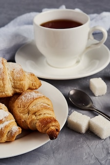 Чашка чая, круассаны, кубики сахара на сером фоне, концепция завтрака
