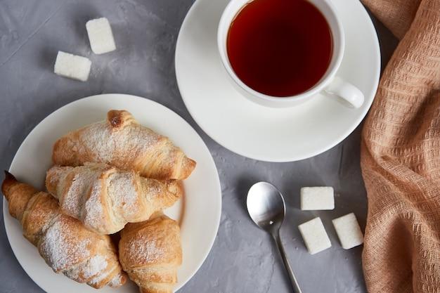 Чашка чая, круассаны, кубики сахара на сером фоне, вид сверху