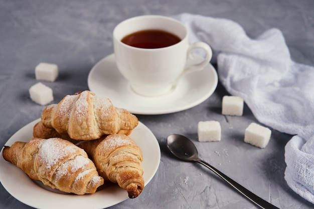 Чашка чая, круассаны, кубики сахара на сером фоне