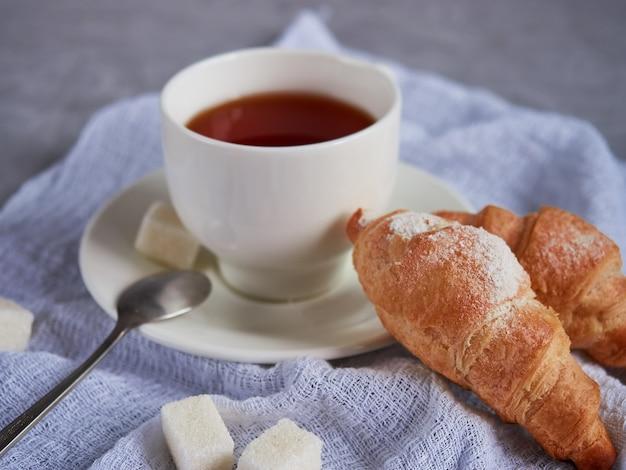 Чашка чая, круассаны, кубики сахара на белой салфетке