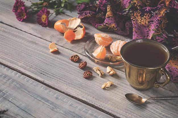 Чашка чая, цветов и мандарина на белом деревянном столе