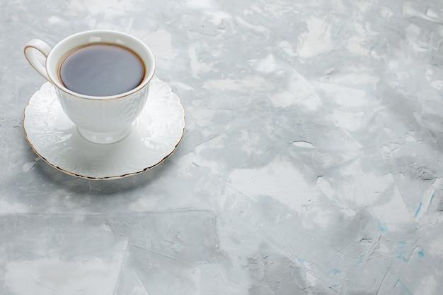 明るい机の上のガラスプレート上の白いカップの中に熱いお茶のカップ、甘いお茶を飲む