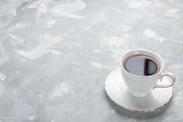 ライトデスクのガラスプレート上の白いカップの中に熱いお茶のカップ、甘いお茶を飲む