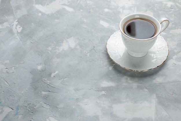 光の上のガラスプレート上の白いカップの中に熱いお茶のカップ、甘いお茶を飲む
