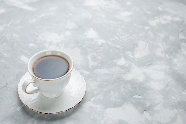 白い机の上のガラスプレート上の白いカップの中に熱いお茶のカップ、甘いお茶を飲む