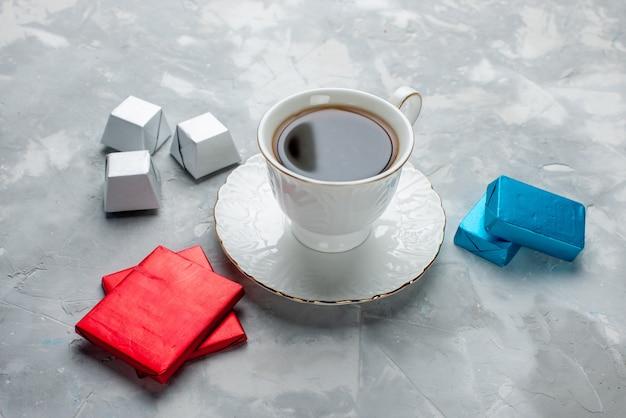 ガラスプレート上の白いカップの中に熱いお茶のカップとライトデスクの上の銀色のパッケージチョコレートキャンディー、お茶を飲む甘いクッキーティータイム
