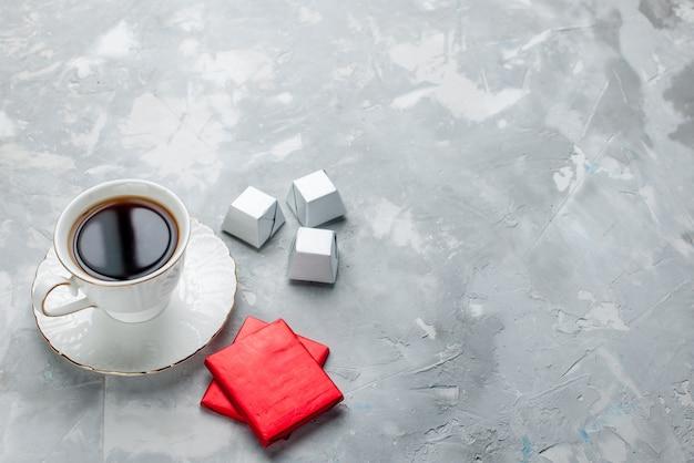 Чашка горячего чая внутри белая чашка на стеклянной тарелке с серебряным пакетом шоколадные конфеты на светлом столе, чайный напиток сладкое шоколадное печенье чаепитие