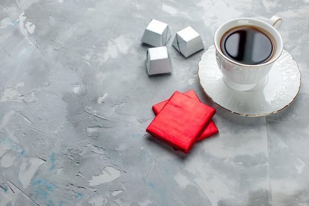 Чашка горячего чая внутри белая чашка на стеклянной тарелке с серебряной упаковкой шоколадные конфеты на светлом столе, чай сладкое шоколадное печенье