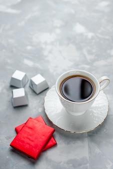 ガラスプレート上の白いカップの中に熱いお茶のカップとシルバーパッケージチョコレートキャンディーライトフロアティードリンク甘いチョコレートティータイム