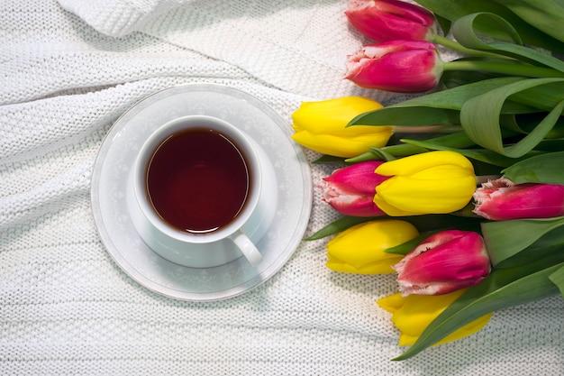 Чашка чая в фарфоровой чашке с букетом цветов желтых и розовых тюльпанов на белой ткани
