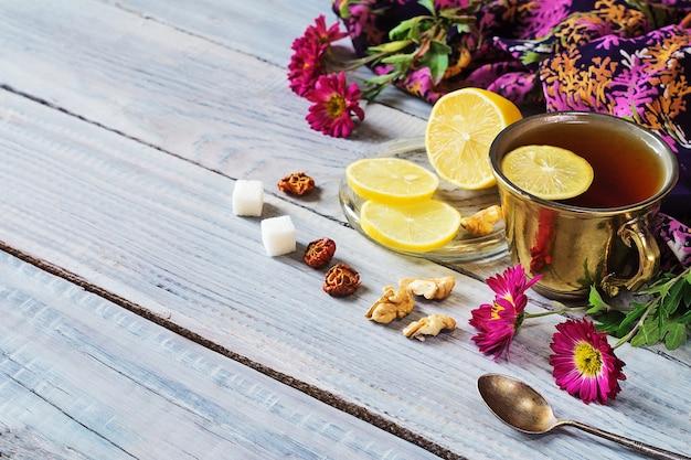 Чашка чая, лимона и цветов на белом деревянном столе