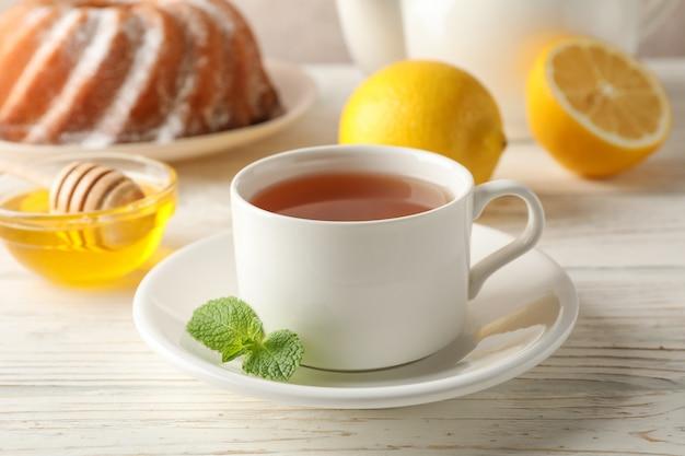 一杯のお茶、レモン、ミント、蜂蜜、ひしゃく、木製のパイ、クローズアップ