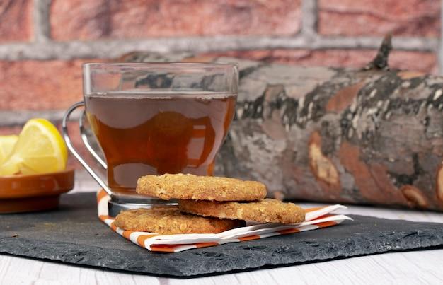 レンガの壁と木の丸太の石のプレートの装飾の上のテーブルにお茶のレモンスライスとオートミールクッキーのカップ。