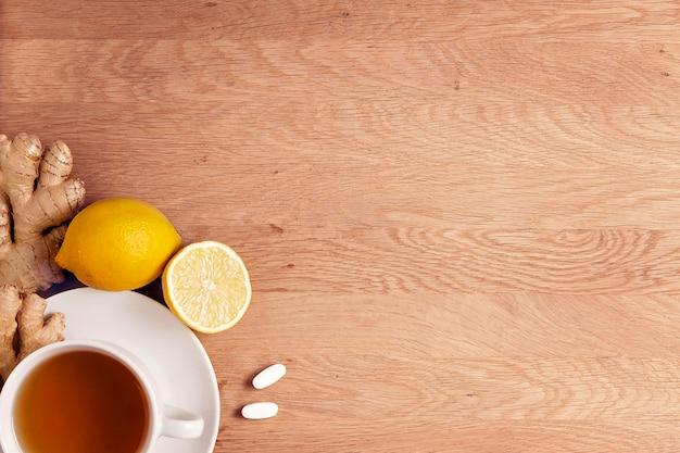 차 레몬 생강 한 컵과 나무 배경 위에 있는 두 개의 보조제 알약 평면도 복사 공간...