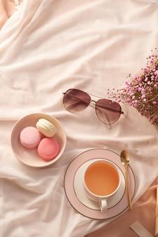 一杯のお茶、マカロンケーキ、グラス、生地の背景に花