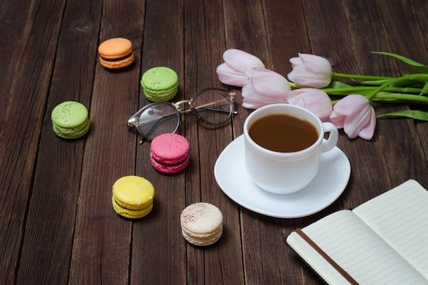 Чашка чая, макароны, бокалы, розовые тюльпаны и блокнот