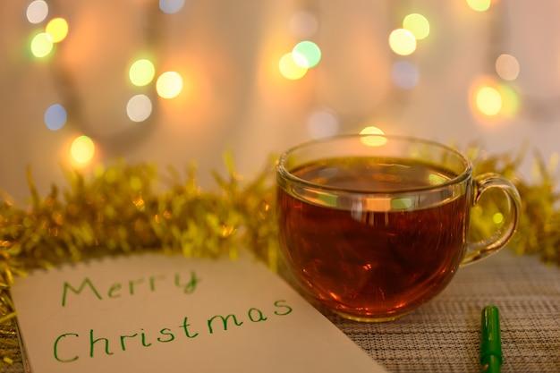Чашка чая, блокнот с надписью merry christmas, украшенный мишурой.