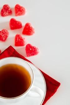 Чашка чая на белом фоне и красный мармелад в форме сердца