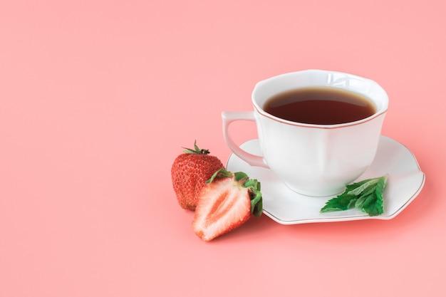 Чашка чая на белом блюдце с листьями мяты и спелой клубники. розовый фон copyspace.